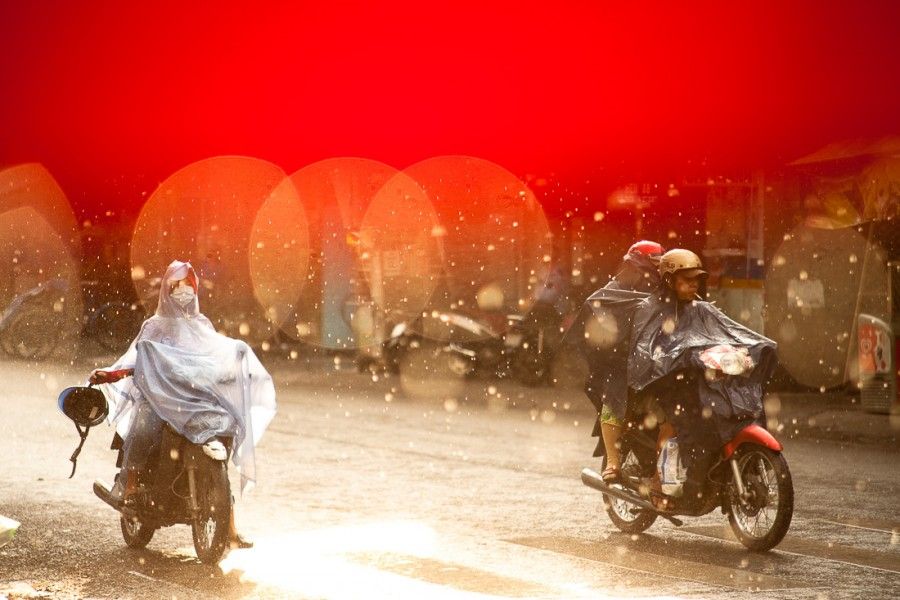 Motorcyclists ride in torrential rain in Saigon, Vietnam. Travel photography by Peter Jackson Photographer.